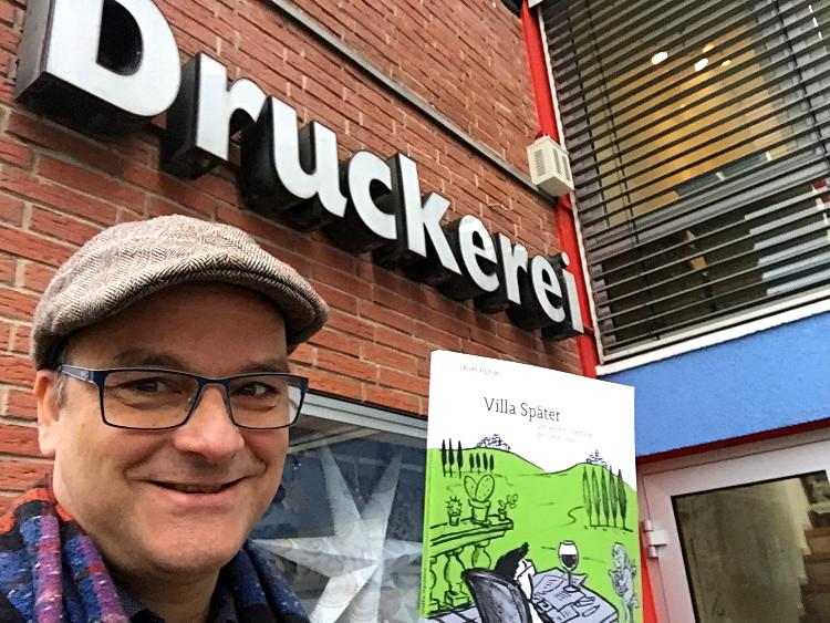 Oliver Hübner mit Buch vor der Druckerei